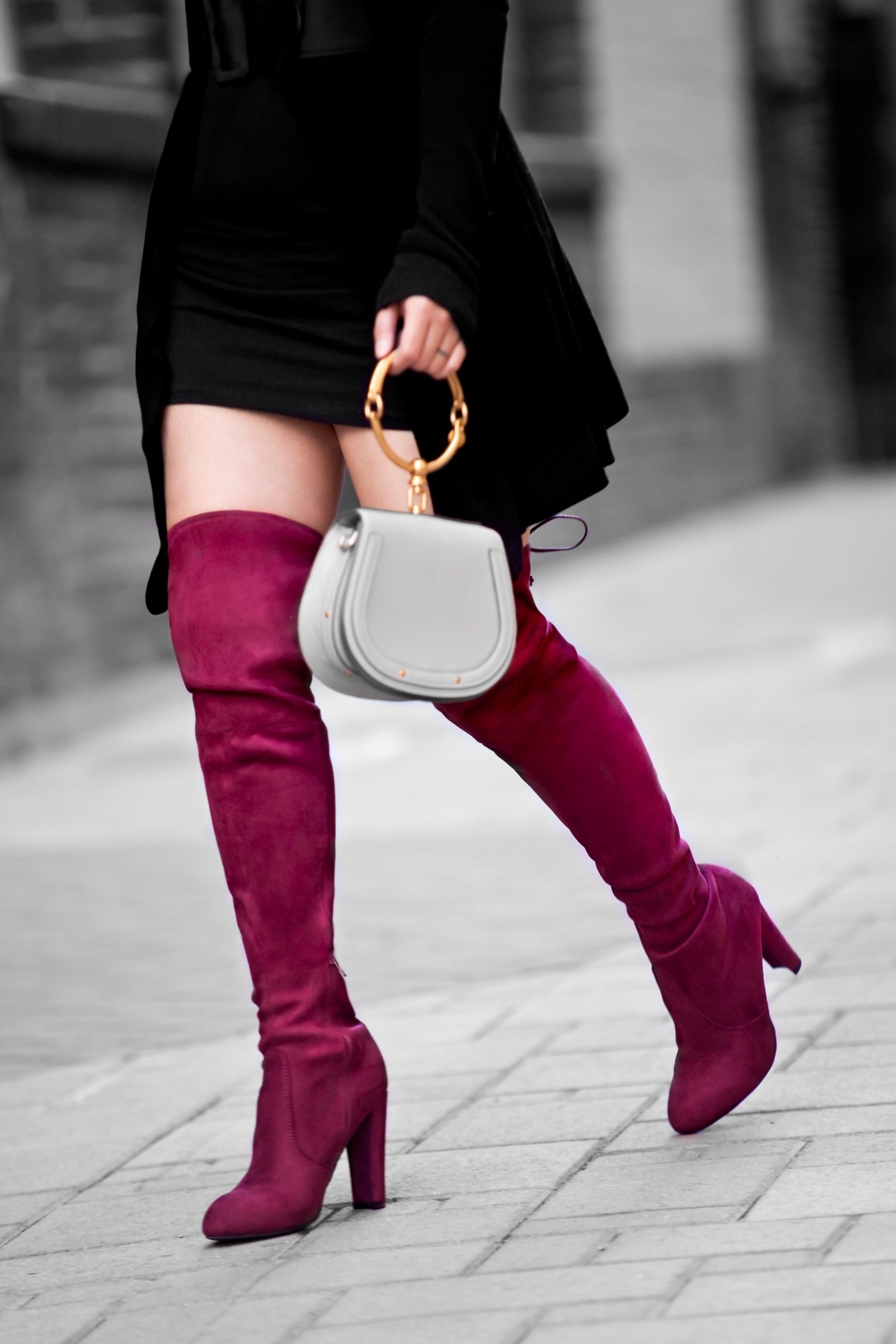 Red over-the-knee boots are all the rage this winter season. Burgundy and bright cherry red make bold statements to any outfit. Get more styling tips at www.theballeronabudget.com