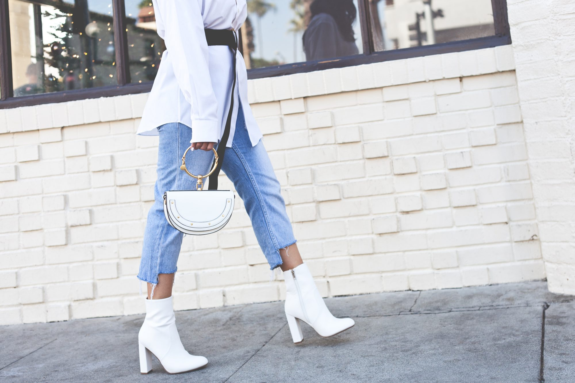 A great way to spice up your outfits with a 70's gogo vibe, you can pair white boots with light wash denim and an oversized sweater for a casual yet chic look. - www.theballeronabudget.com