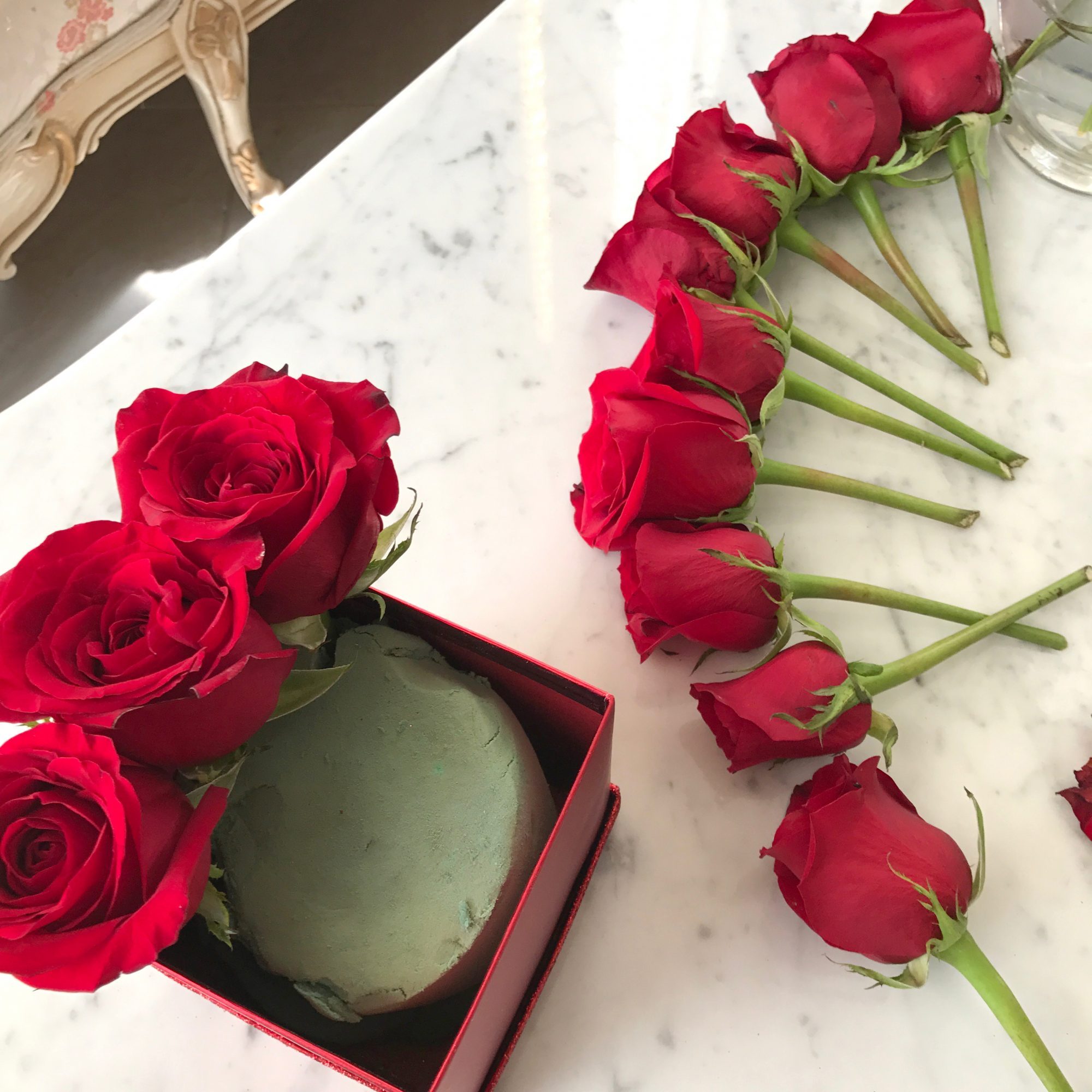 Step 1: Cut the stems of the roses so that the bulbs will sit above the box. Make sure to pick off any dying or blemished petals. - www.theballeronabudget.com