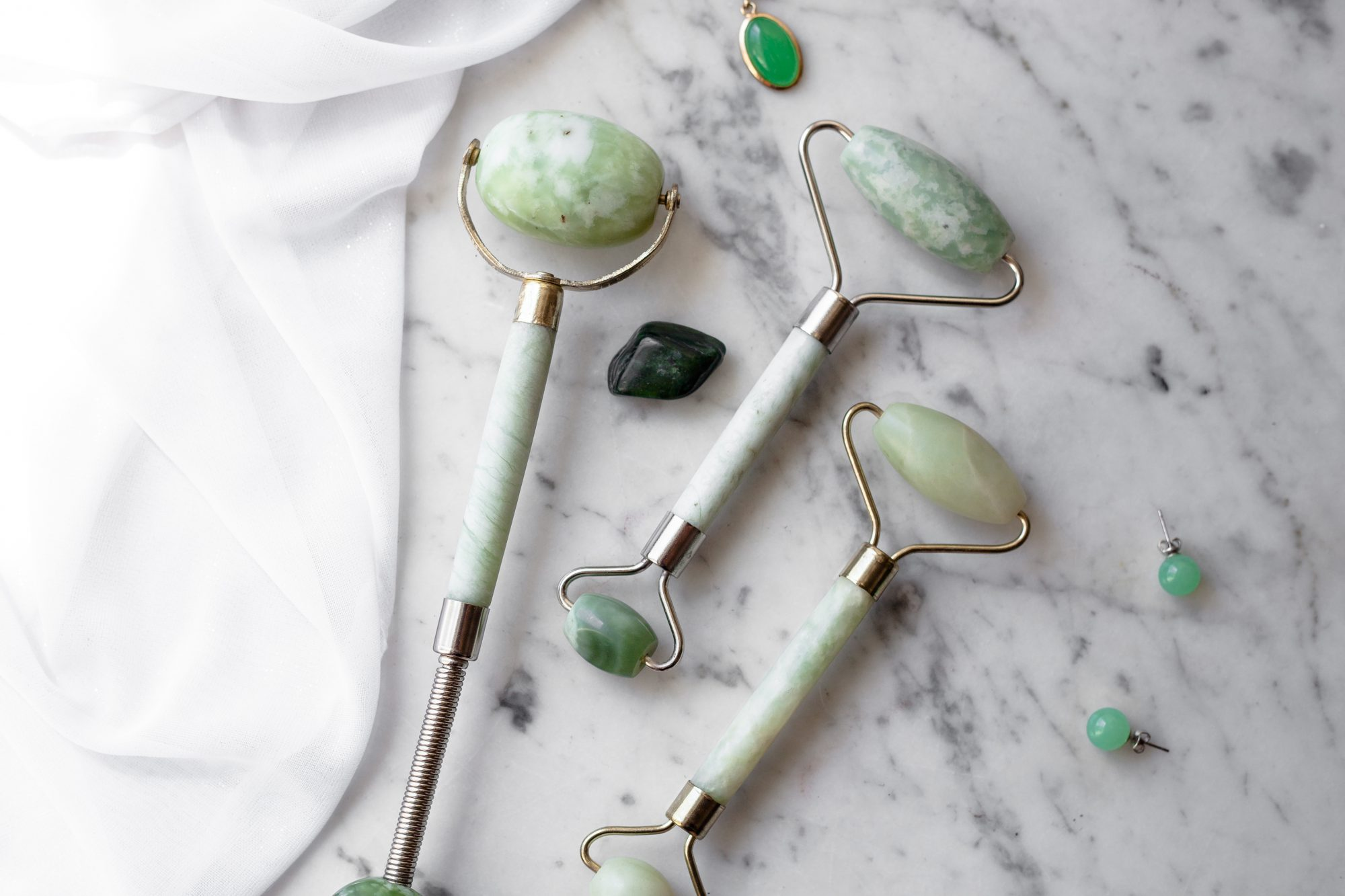 The top-most charm is fake jade, while the bottom stud earrings are real. The dark stone is real nephrite jade. What do you think the jade rollers are made of? - www.theballeronabudget.com