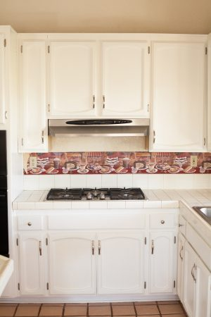 After image of kitchen stove cabinets painted with white milk paint