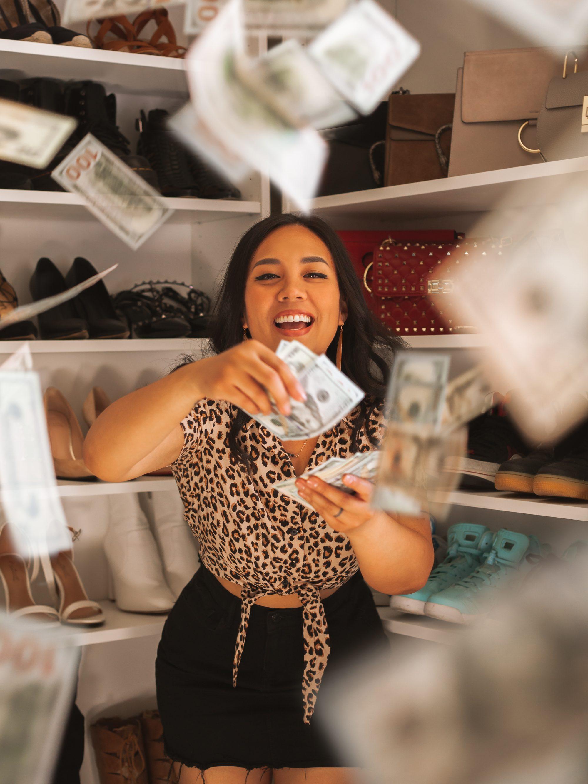 Rich woman throwing dollar bills in the air