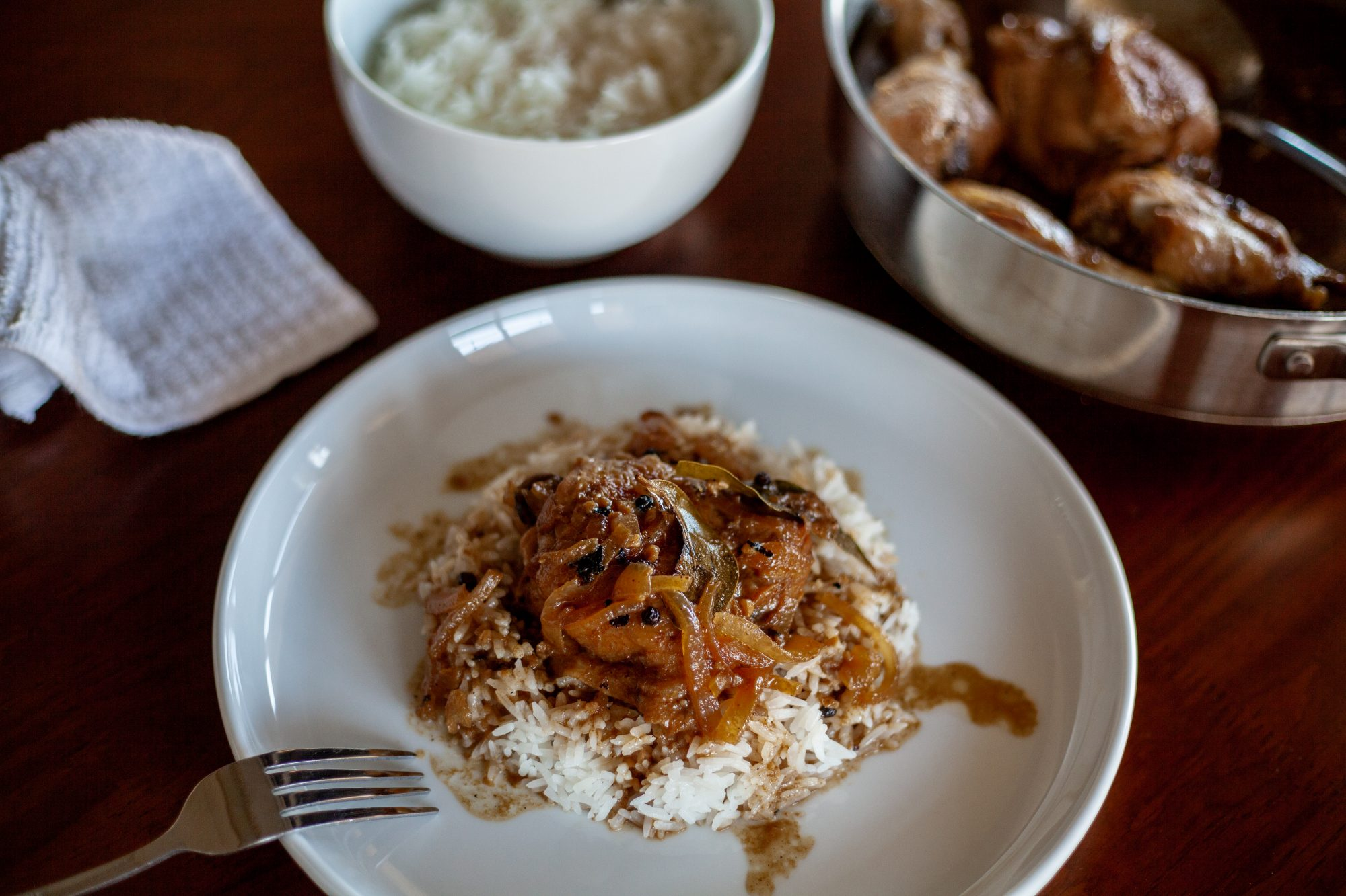 Filipino Adobo Chicken on a dish served on a dinner tablecape with a bowl of rice