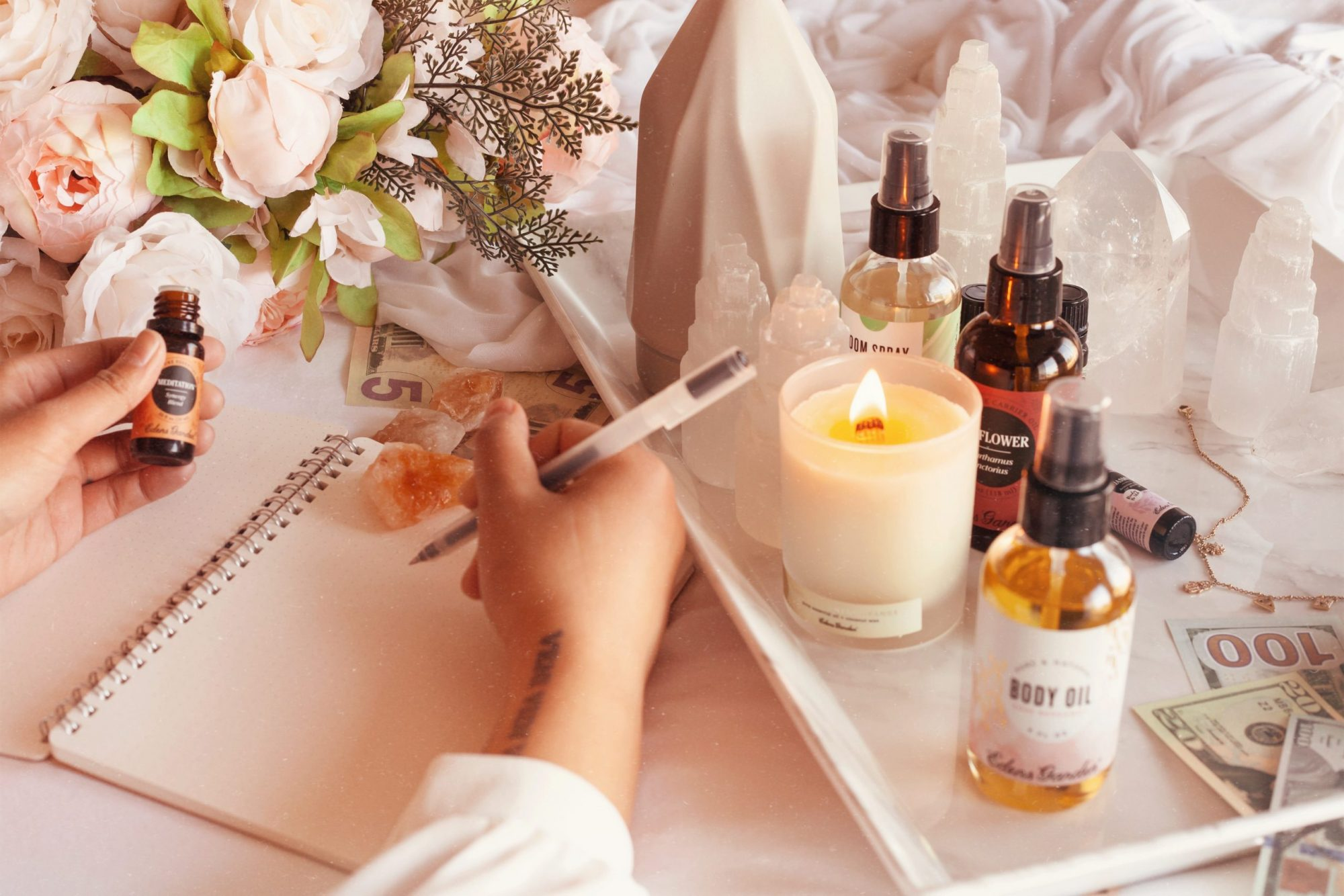 Image of essential oils, oil diffuser, candle, and writing in a journal