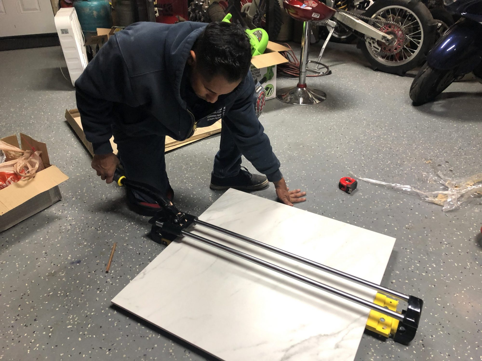 Jun using a large format tile cutter to cut down a 30x30 tile into 14x14 tiles
