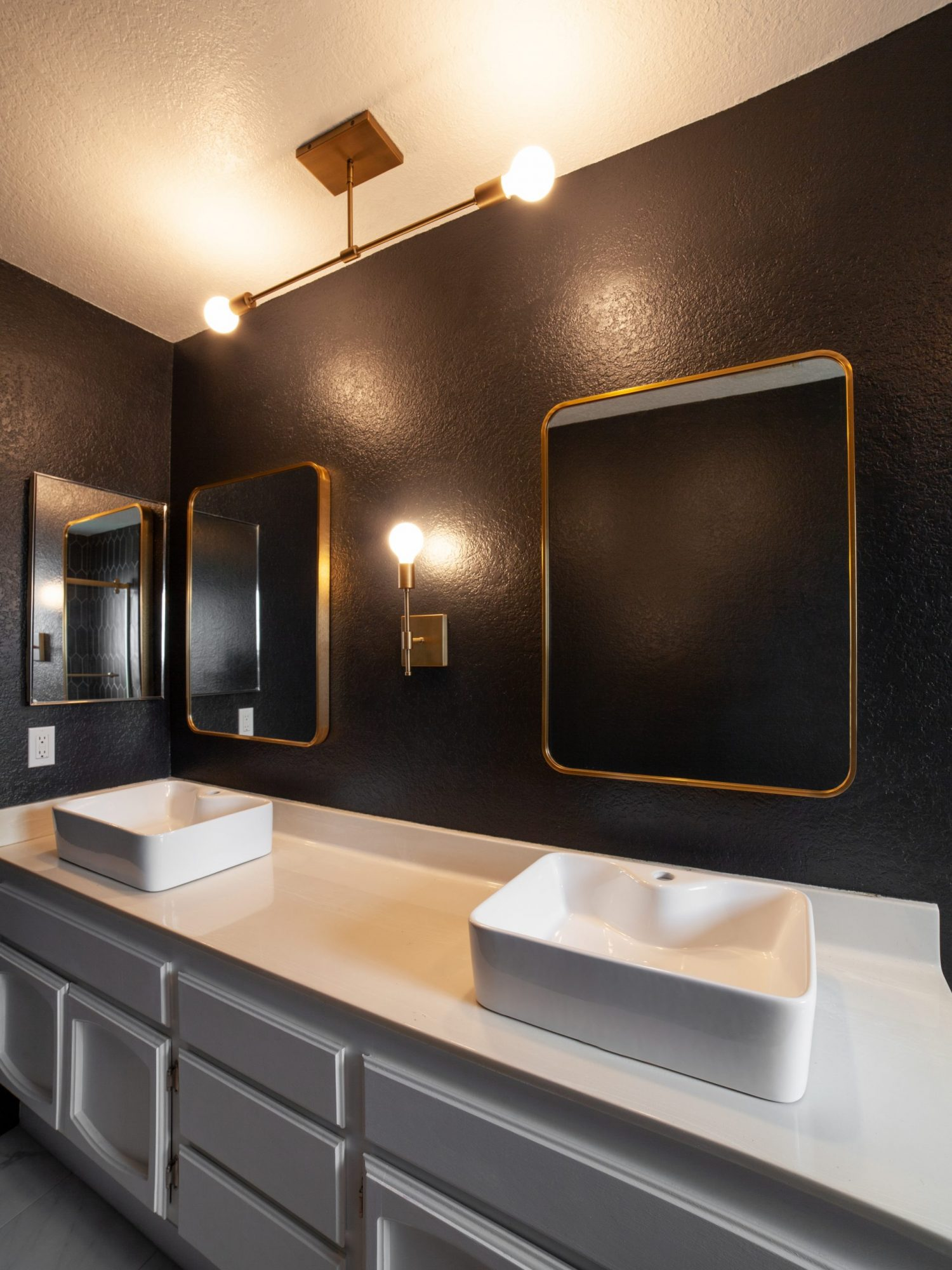 Black and white bathroom renovation with gold fixtures